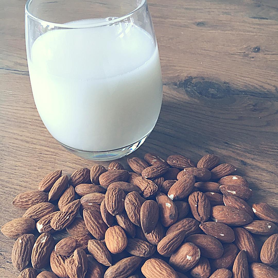 et glas med hjemmelavet mandelmælk og mandler