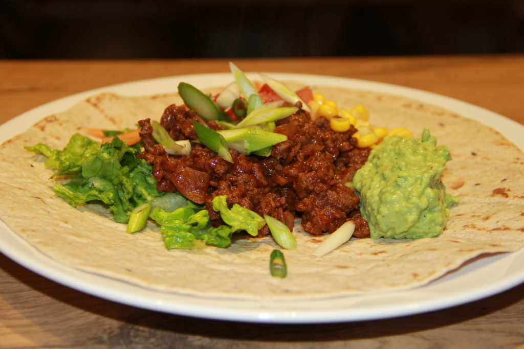 tortilla med oksekødsfyld, guacamole og grøntsager