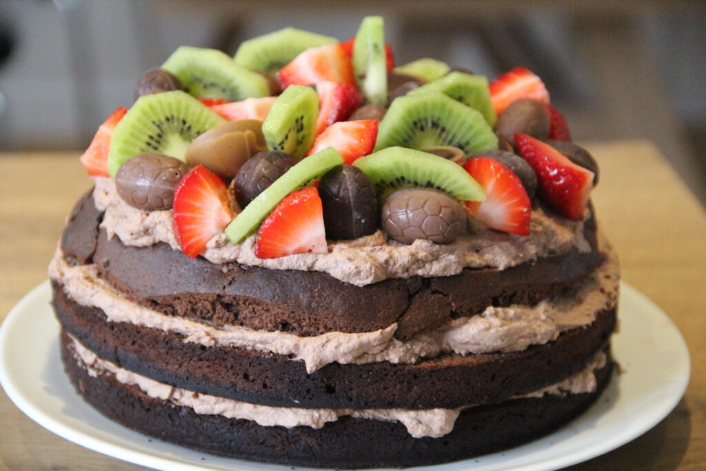chokolade lagkage med pynt af slik, frugt og bær